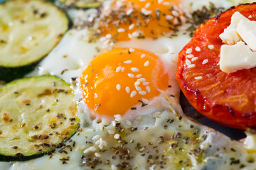 Image of plate with fried eggs with tomatoes and zucchini