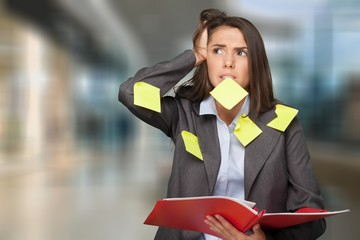 Businesswoman standing with copybook and sticky notes