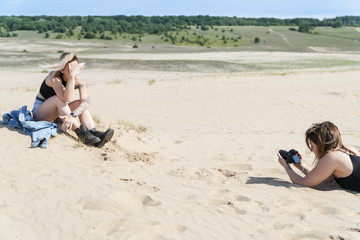 Process of photographing the model in the sands near the forest on the horizon