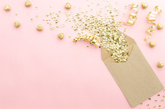 Envelope with gold glitter sequins, confetti and hearts on a gently pink background. Mockup template. View from above