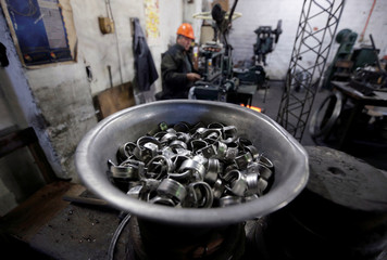 An employee of a factory for household items works with aluminium utensils in Capiata