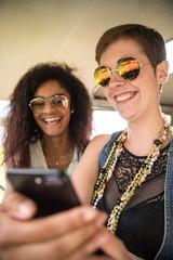 Two young women having fun watching videos on a phone