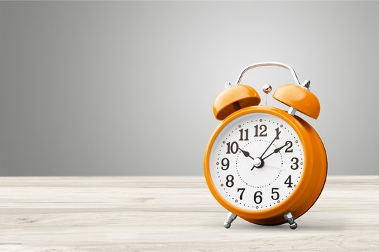 Orange retro alarm clock on wooden table