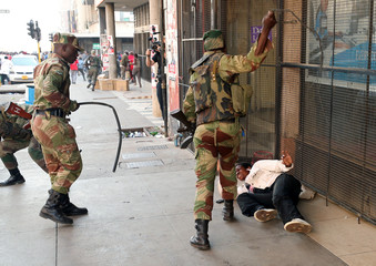 Soldiers beat a supporter of the opposition Movement for Democratic Change party of Nelson Chamisa outside the party's headquarters as they await the results of the general elections in Harare