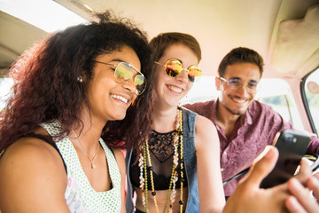 Mixed group of happy young people in a camper van having fun