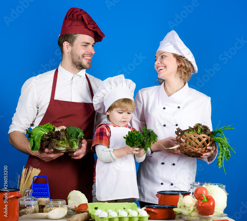 Child with parents cooking at kitchen table  Happy loving