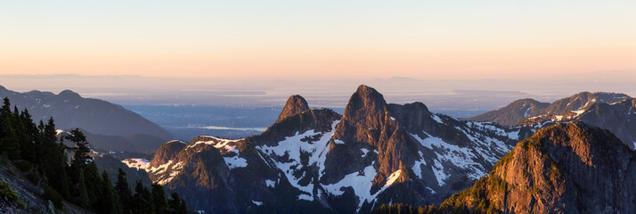 Panoramic landscape view of The Lions Peaks during a vibrant summer sunrise. Taken from the top of Brunswick Mountain, North of Vancouver, BC, Canada.
