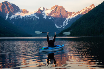 Adventurous man kayaking in the water surrounded by the Beautiful Canadian Mountain Landscape. Taken in Jones Lake, near Hope, East of Vancouver, BC, Canada.
