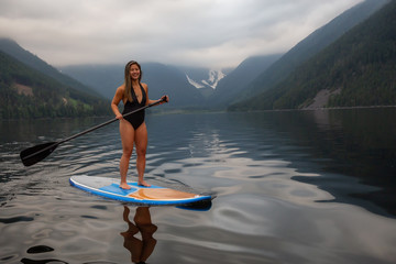 Young woman on a paddle board during a cloudy evening. Taken in Jones Lake, near Hope and Chilliwack, East of Vancouver, BC, Canada.