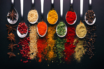Spices and condiments for cooking on a black background