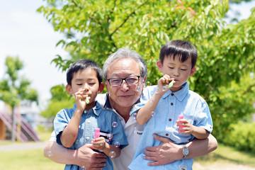 公園でシャボン玉を楽しむ孫を抱きしめるシニア男性