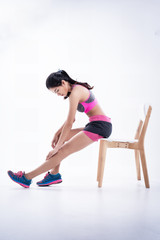 The beauty lady is wearing exercise suit,doing exercise by sitting on chair and stretch left leg forward,basic pattern for exercise.