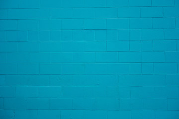 Concrete cinder block wall painted turquoise blue.