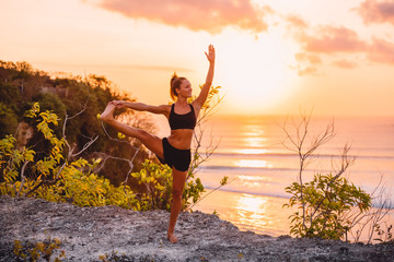 Sporty woman practicing yoga at sunset or sunrise with ocean at background