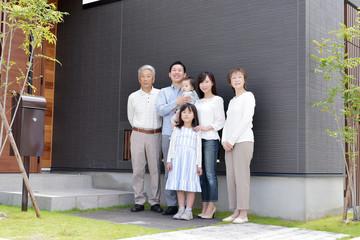 自宅前に並ぶ3世代家族