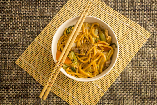 Fried noodle.  Yakisoba with beef, ticken and vegetables in a white bowl on a dark background. Asian cuisine meal.