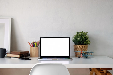 Stylish workspace with laptop, office supplies and mockup poster on white wooden desk.