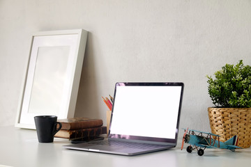 Stylish workspace with laptop and mockup poster on white wooden desk.
