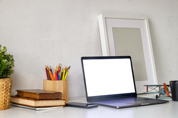 Mockup laptop with poster on wooden desk and graphic display mockup.