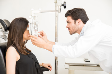Attractive ophthalmologist examining woman patient eyes in laboratory room