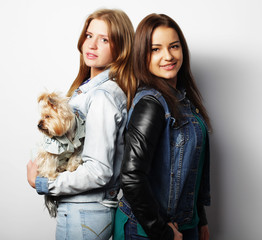 lifestyle and people concept: Two young girl friends standing together and holding dog