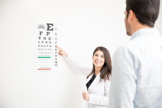 Eye specialist using Snellen test to examine patient