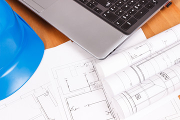 Electrical blueprints with laptop for engineer jobs and protective blue helmet, technology concept