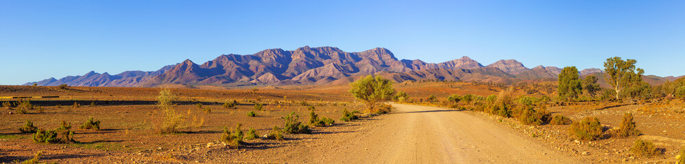 Poster Blue sky Gravel countryside road leading to rugged peaks of Flinders Ranges mountains in South Australia