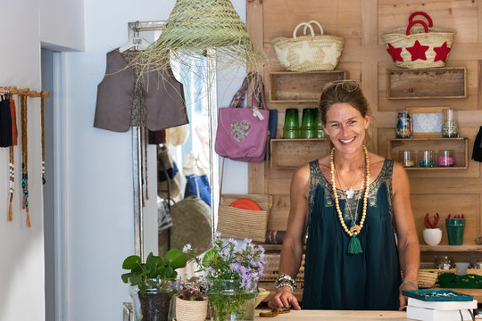 Portrait of a french blonde mature woman smiling at her store, entrepreneur concept.