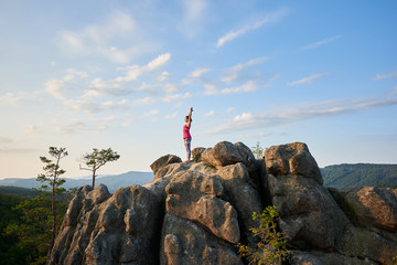 Attractive girl standing with raised hands in yoga pose on top of rocky mountain on green tree tops and clear blue sky background in the summer morning. Sport, yoga and healthy lifestyle concept.