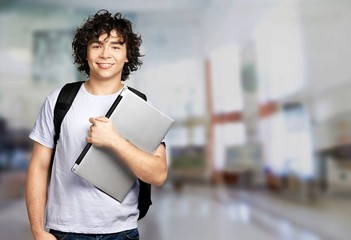Male student with laptop on background