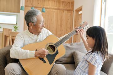 リビングのソファで孫娘とギターを弾くシニア男性