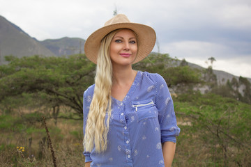 Beautiful blond woman wearing the hat outdoors in the prairie