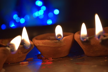 diwali diya lamp made of mud with oil in it with blue bokhed background
