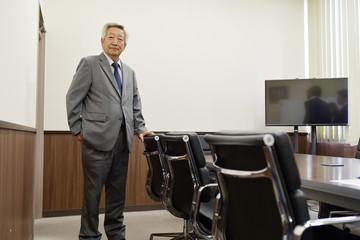 会議室に立つシニアビジネスマン