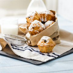 Cupcakes with raisins, powdered sugar on wooden table with milk