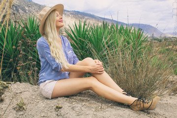 Beautiful blond woman in a hat. Sits in the fresh air on the prairie. Mysteriously smiling and looking at the sky