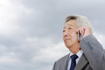 スマホで会話するシニアビジネスマン