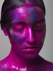 Woman space. A creative make-up of the person by means of bright paints and the poured pigments. Halloween, holidays, studio of beauty and art