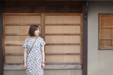 木造の家と女性