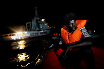 A migrant sits on board the NGO Proactiva Open Arms rescue boat in the central Mediterranean Sea