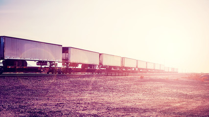 Intermodal freight transport, semi trailers on train at sunset, color toned picture, USA.
