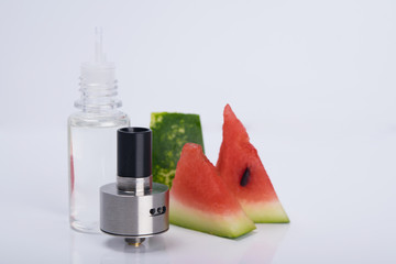 on a white background pieces of watermelon, liquid for refueling, e-cigarette tank.