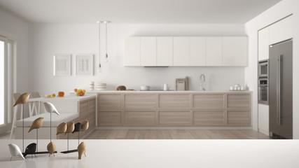 White table top or shelf with minimalistic bird ornament, birdie knick - knack over blurred contemporary scandinavian wooden kitchen, modern interior design