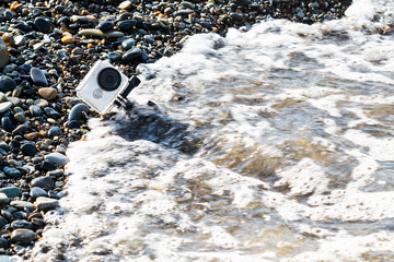 White action camera in underwater case with selfie stick. Action camera in water on the pebble beach