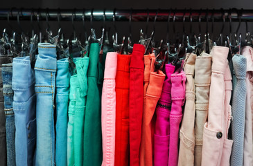 Many colorful fabric jeans are hanging on the clothesline, as abstract color fashion background.