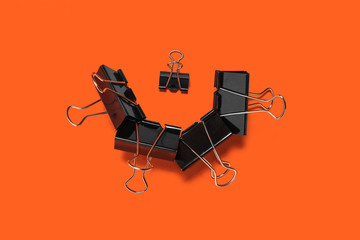 collection of paper clips for office stationery lying on the orange background. concept of business or educational equipment
