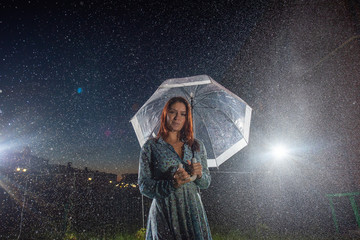 Sad young woman in a dress in the rain with a transparent umbrella at night. Beautiful woman with a transparent umbrella in the lanterns and rain drop