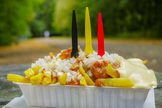 Traditional Belgian fast food, fried potatoes chips with mayonnaise, sate souse and onion served outside