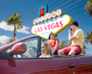 summer holidays, road trip and travel concept - happy friends driving in convertible car and taking picture by film camera over welcome to fabulous las vegas sign background